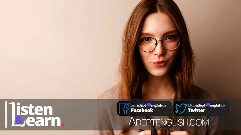 Photo of young beautiful woman in eyeglasses posing and looking at camera isolated over grey wall.