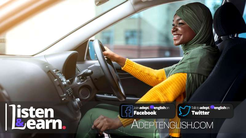 Portrait photograph of a happy African Muslim woman in headscarf in new car, part of this English conversation listening practice lesson.