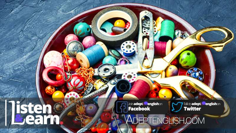 A photograph of colourful beads, different shaped beads and tools used in producing fashionable clothing.