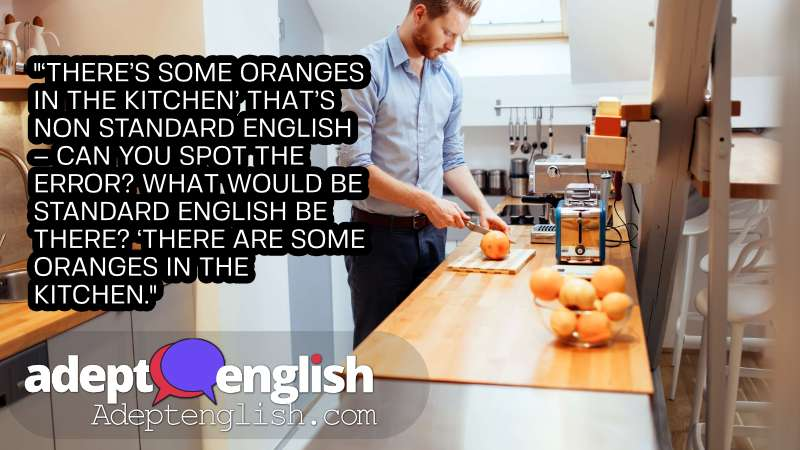 A photograph of a man slicing oranges in a kitchen. The standard and non standard English way of saying there are oranges in the kitchen.