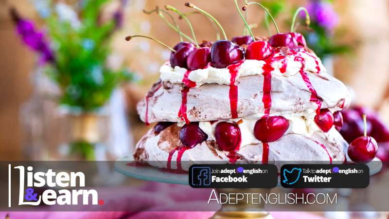 A photograph of a black forest Pavlova cake with a cherry on top, used to help explain the English idiom the cherry on top of the cake.