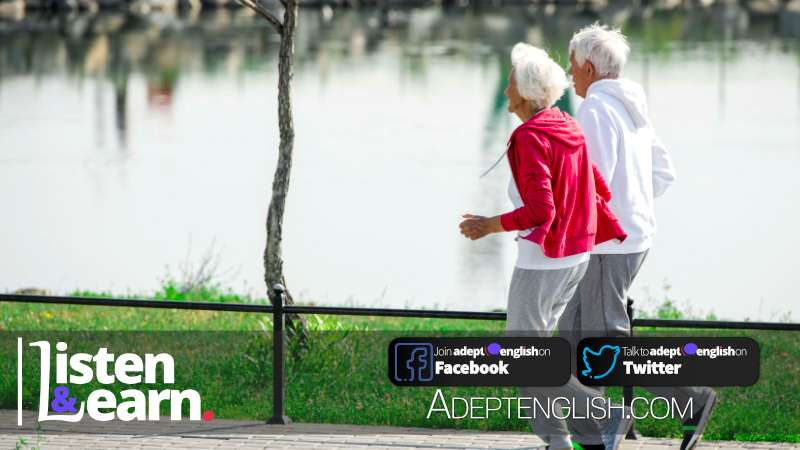 A side view full length portrait photograph of active senior couple running in park along lake. As we talk about longevity in our English lesson today.