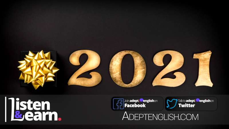 Happy New year 2021 from Adept English. Champagne glasses and and text happy new year 2021 on wooden table.