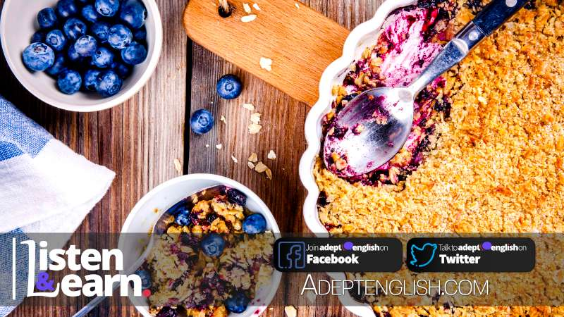 A photograph of a British home-made blueberry crumble with oatmeal, learning to speak English and how to cook yummy food.