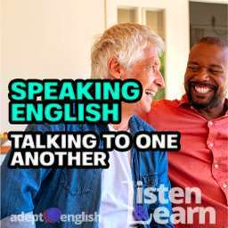 A photograph of men smiling as they have a conversation in English together.
