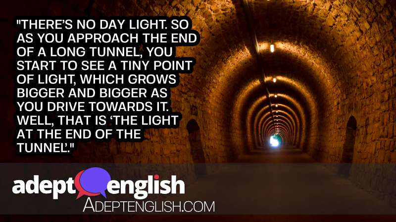 A photograph of a long underground tunnel with stone walls and in the distance a bright tunnel exit into the daylight beyond. Used to help explain the English language idiom of light at the end of the tunnel.