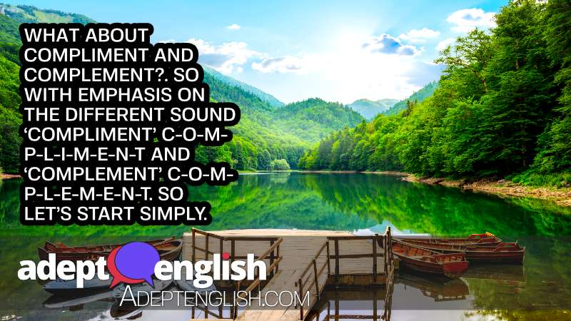 A stunning picture of a lake in the mountains, with wooden boats on the water in the foreground and mountains and forest in the distance. Used as an article image for the article Learn English, Speak Fluently And Understand Everything You Hear: Homophones Article Image