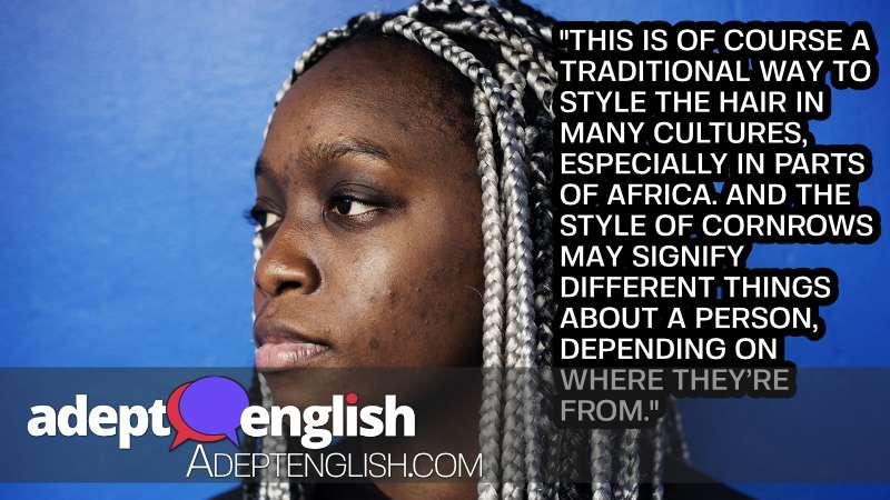 A portrait photograph of a black woman with cornrow hair.