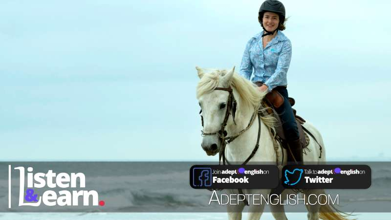 A photograph of a lady riding a white horse on sand at the beach. Used in an English language listening story to help students talk English.