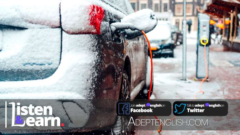 A photograph of an electric car on charge on a main street covered in snow on a very cold day. Used as cover art for the how to learn English lesson talking about electric cars in the UK.